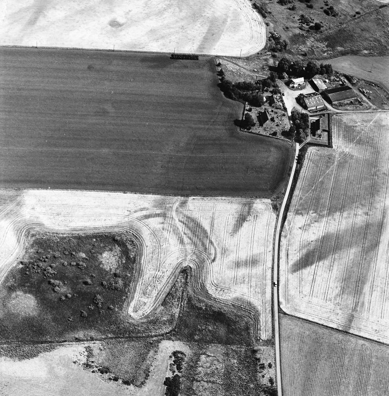 Gilchrist, oblique aerial view, taken from the WNW, centred on the cropmarks of a promontory fort. Kilchrist Church is visible in the top right-hand corner of the photograph.