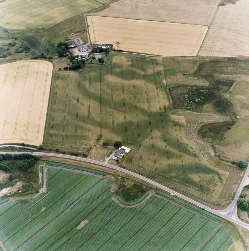 Oblique aerial view centred on the cropmarks of the possible pit-defined enclosure, pits, linear cropmarks and promontory fort with church, mausoleum and cemetery adjacent, taken from the N.