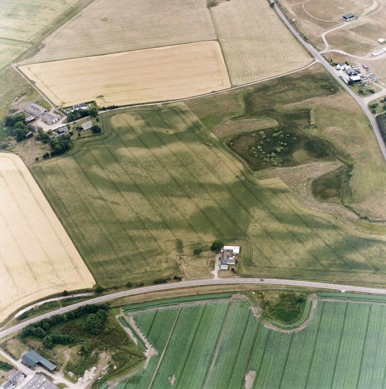 Oblique aerial view centred on the cropmarks of the possible pit-defined enclosure, pits, linear cropmarks and promontory fort with church, mausoleum and cemetery adjacent, taken from the NE.