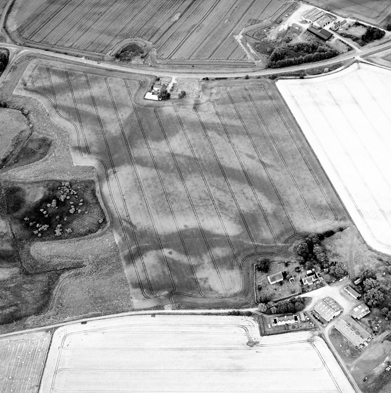 Oblique aerial view centred on the cropmarks of the possible pit-defined enclosure, pits, linear cropmarks and promontory fort with church, mausoleum and cemetery adjacent, taken from the SSW.