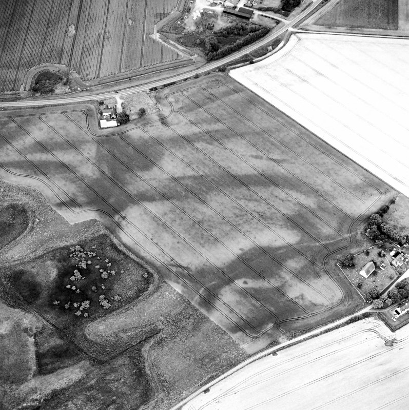 Oblique aerial view centred on the cropmarks of the possible pit-defined enclosure, pits, linear cropmarks and promontory fort with church, mausoleum and cemetery adjacent, taken from the SW.