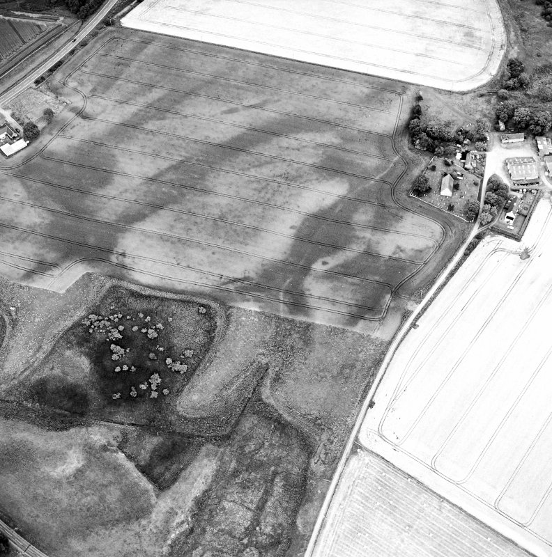 Oblique aerial view centred on the cropmarks of the possible pit-defined enclosure, pits, linear cropmarks and promontory fort with church, mausoleum and cemetery adjacent, taken from the W.