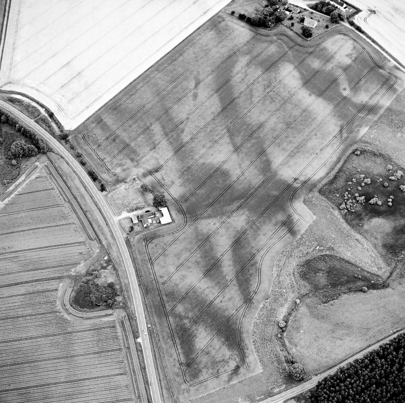 Oblique aerial view centred on the cropmarks of the possible pit-defined enclosure, pits, linear cropmarks and promontory fort with church, mausoleum and cemetery adjacent, taken from the NW.