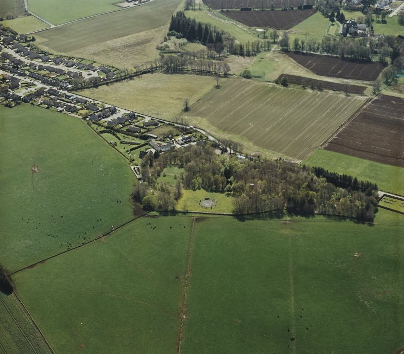 Oblique aerial view centred on the remains of the recumbent stone circle and enclosed cremation cemetery, taken from the NE.