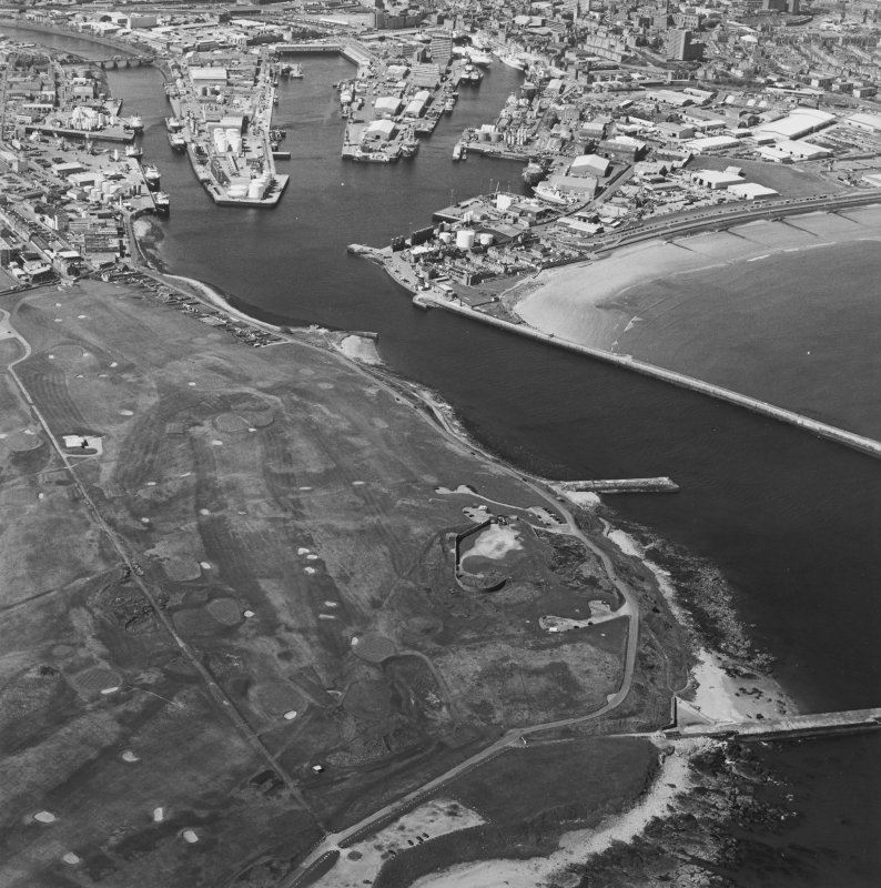 Oblique aerial view centred on the remains of the coastal battery with breakwaters adjacent and harbour in background, taken from the E.