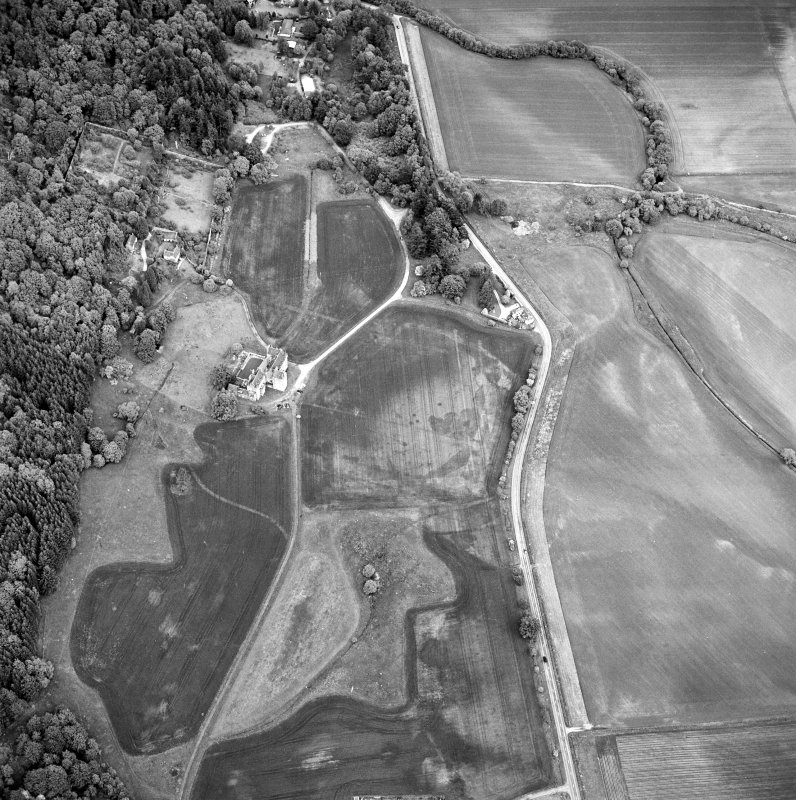 Oblique aerial view of Castle Menzies centred on a tower house, well, walled garden and military road, and the crop marks of pits, a garden and linear cropmarks, taken from the WSW.
