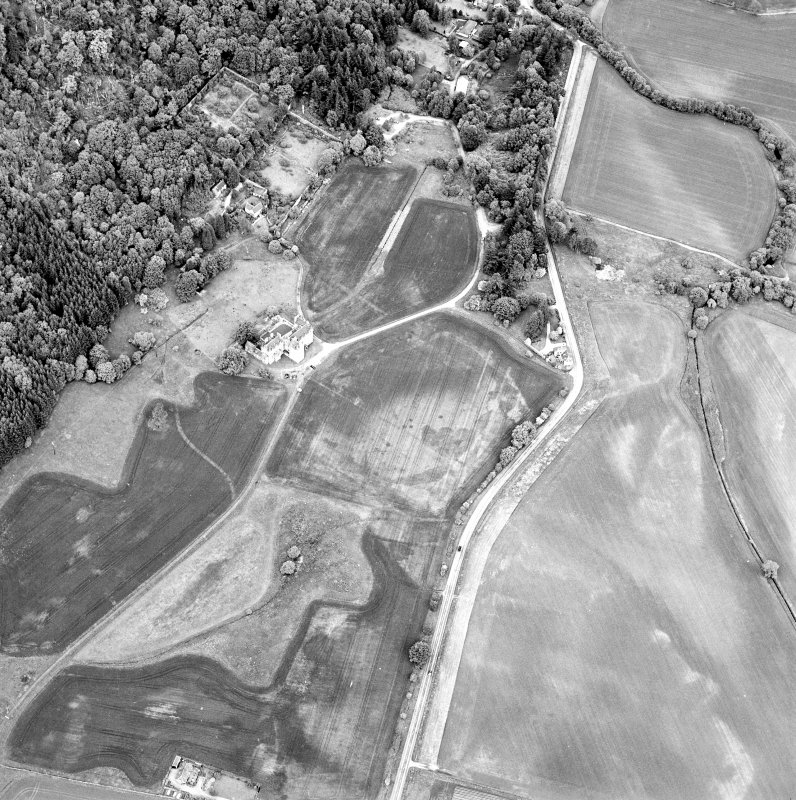 Oblique aerial view of Castle Menzies centred on a tower house, well, walled garden and military road, and the crop marks of pits, a garden and linear cropmarks, taken from the SW.