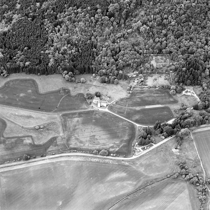 Oblique aerial view of Castle Menzies centred on a tower house, well, walled garden and military road, and the crop marks of pits, a garden and linear cropmarks, taken from the SSE.