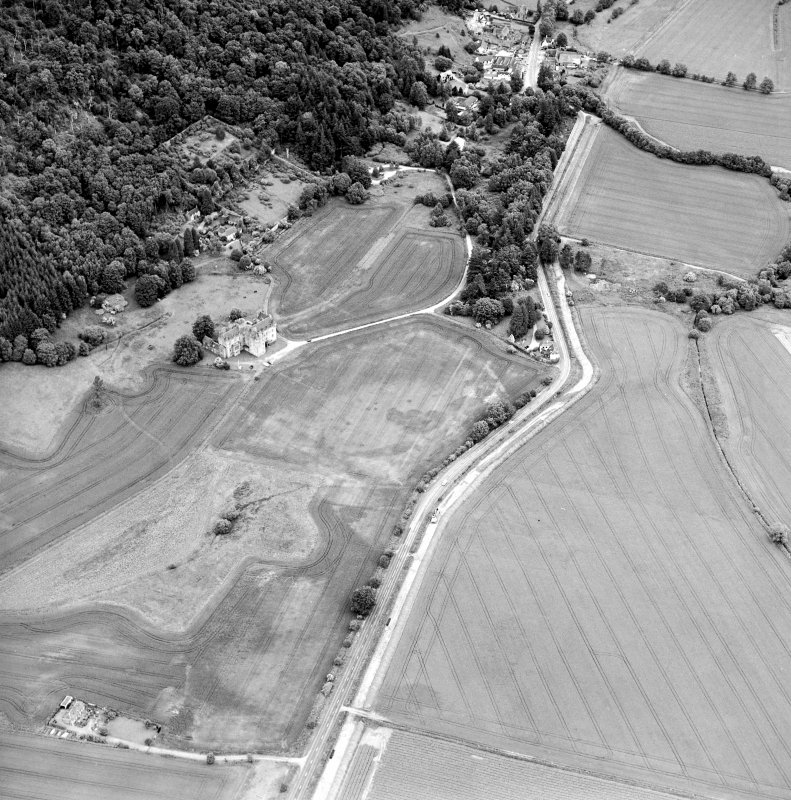 Oblique aerial view centred on the cropmarks of pits and linear cropmarks, with tower house, pits and walled garden adjacent, taken from the SW.
