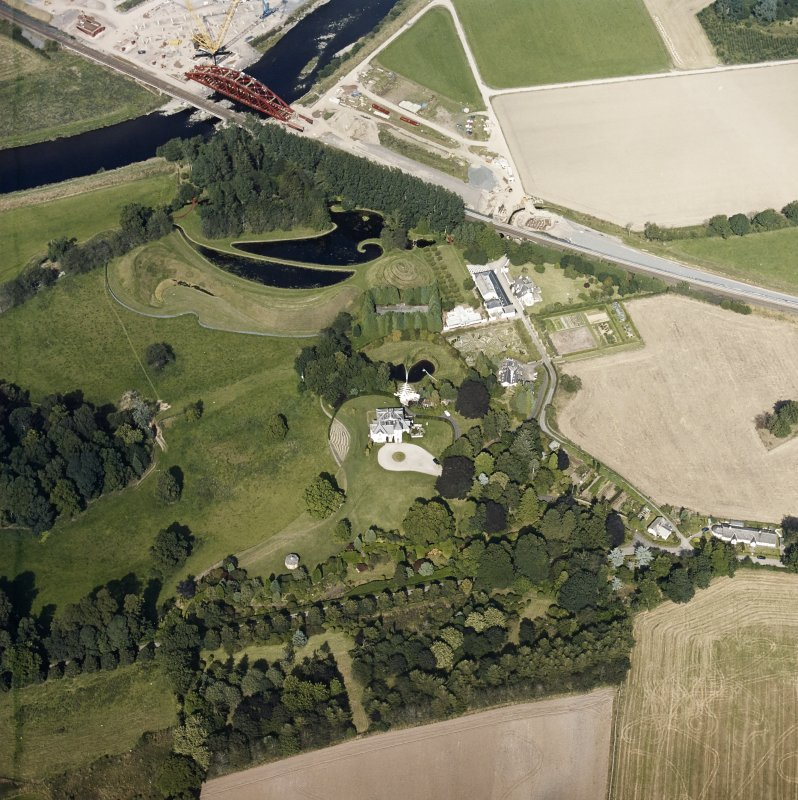 Oblique aerial view centred on the country house and garden with the lodge, railway viaduct and construction works adjacent, taken from the SW.