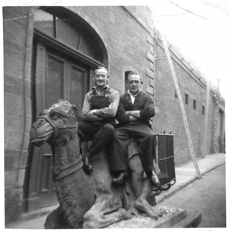 The famous camel sat above the entrance archway to the works. The archway was dismantled in June 1955, and employees took the opportunity to be photographed sitting on the camel. One of the two men in this photo is James Dixon, a metalworker at the works.