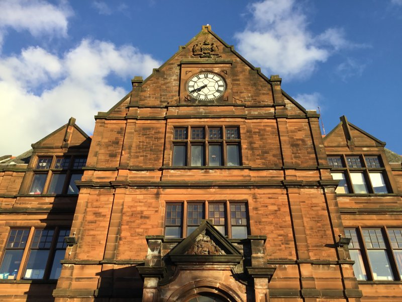 This picture is of the main entrance to the Old Kilmarnock Academy building originally constructed in 1898. It features Kilmarnock's coat of arms and a clock which can be seen both on the outside and inside of the building. The windows that can be seen in the photos are tinted maroon and gold referencing the most prominent colours in the school's emblem. This photo was taken by Dylan Masson, S2 pupil at Kilmarnock Academy 2017.
