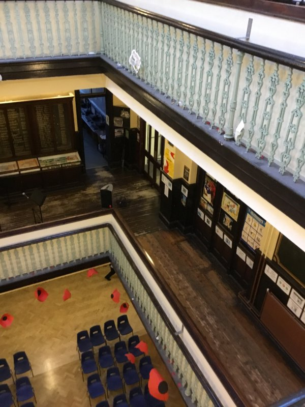 This photo was taken from the third floor of Kilmarnock Academy just before remembrance day hence the poppies hanging from the second floor. At the top of the picture is the banister of the third floor. Looking a floor down you can see a few classrooms with laminated pictures. Also on the second floor is a dux board with names of former pupils. On the bottom floor you can only really see chairs in this photograph. This photo was taken by Chloe Morfitt, S1 pupil at Kilmarnock Academy 2017.