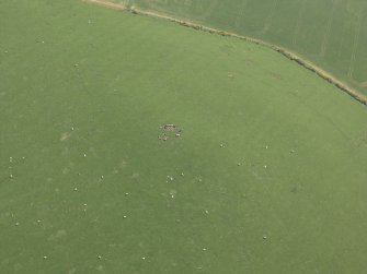 Oblique aerial view centred on the remains of the recumbent stone circle and rig, taken from the N.