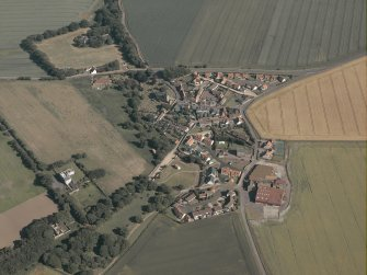 General oblique aerial view of the village with the manse adjacent, taken from the NW.