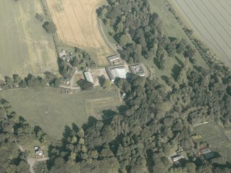 Oblique aerial view centred on the country house and the farmsteading, taken from the W.