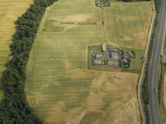 Oblique aerial view centred on the cropmarks of the Roman temporary camp and the farmhouse and farmsteading, taken from the WSW.