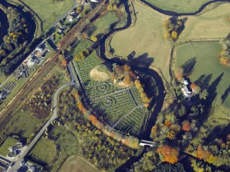 Oblique aerial view centred on the remains of the motte and bailey castle and the cemetery, taken from the SE.