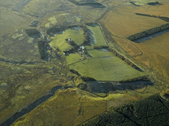 Oblique aerial view centred on the farmhouse and remains of the rig, taken from the NE.