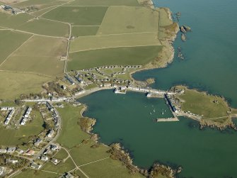 General oblique aerial view centred on the village with the tower house and remains of the promontory fort and chapel adjacent, taken from the SW.
