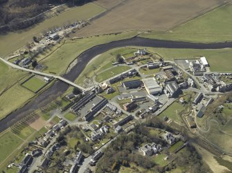 Oblique aerial view centred on the woollen mill with the road bridge and convent  adjacent, taken from the NE.