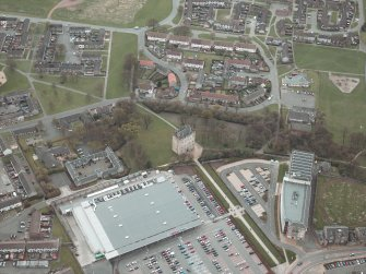 Oblique aerial view centred on the tower-house, stables and mills, taken from the NNW.