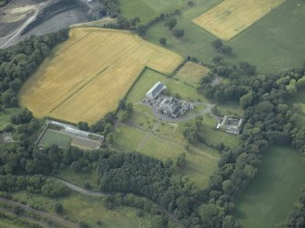 Oblique aerial view centred on the country house, formal garden and stables, taken from the SE.