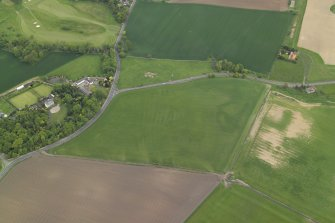 Oblique aerial view centred on the cropmarks of the rig with the country house, walled garden and cropmarks of the possible enclosure adjacent, taken from the SW.