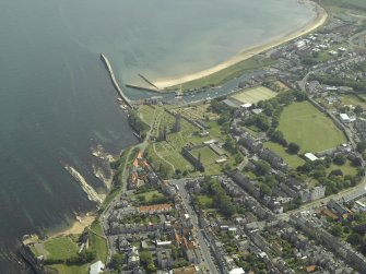 Oblique aerial view centred on the remains of St Andrews cathedral with the school, harbour and remains of the castle adjacent, taken from the WNW.