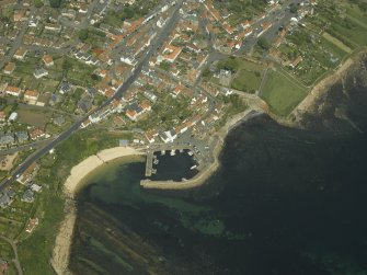 General oblique aerial view of the town centred on the harbour, taken from the S.