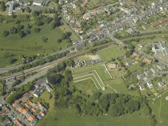 Oblique aerial view centred on the remains of the castle, dovecot and walled garden and the church and burial-ground, taken from the S.