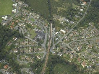Oblique aerial view of the village centred on the railway station and school, taken from the SSE.