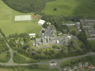 Oblique aerial view centred on the school, church, hospital and house, taken from the W.