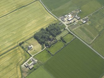 Oblique aerial view centred on the remains of the castle and tower-house, taken from the NE.