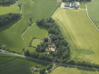 Oblique aerial view centred on the castle, tower-house and steading with the watermill adjacent, taken from the E.