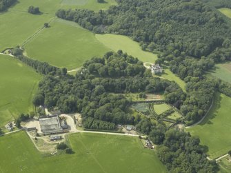General oblique aerial view centred on the castle, tower-house, walled garden and farmsteading, taken from the SE.