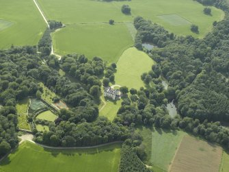 Oblique aerial view centred on the castle, tower-house and walled garden, taken from the NE.