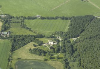 Oblique aerial view centred on the country house, dovecot, and remains of the chapel with the farmhouse, farmsteading and walled garden adjacent, taken from the S.
