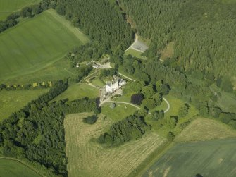 Oblique aerial view centred on the country house, dovecot, and remains of the chapel, taken from the WSW.