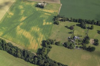 Oblique aerial view centred on the cropmarks of the Roman fortress and ring-ditch with the country house, farmhouse and farmsteading adjacent, taken form the NW.