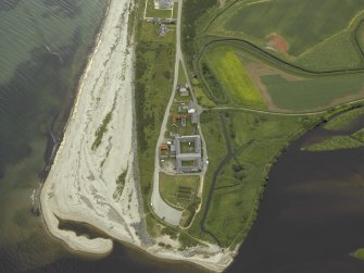 Oblique aerial view centred on the fishing station, ice-house, farmhouse and farmsteading, taken from the W.