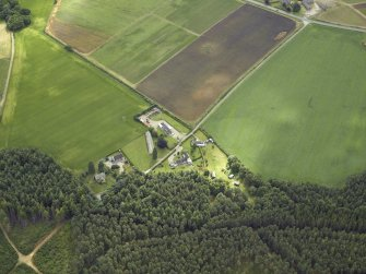 Oblique aerial view centred on the church and the farmsteading, taken from the W.