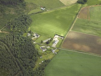 Oblique aerial view centred on the church and the farmsteading, taken from the SSW.