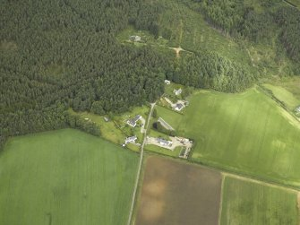 Oblique aerial view centred on the church and the farmsteading, taken from the SE.