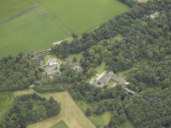 Oblique aerial view centred on the country house, stables and bridge, taken from the NW.