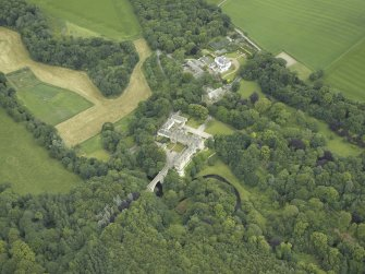 Oblique aerial view centred on the country house, stables and bridge, taken from the SSW.
