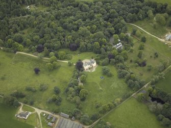 Oblique aerial view centred on the country house with the farmhouse adjacent, taken from the WSW.