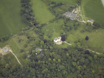 Oblique aerial view centred on the country house with the farmhouse and farmsteading adjacent, taken from the NE.