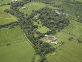 General oblique aerial view centred on the farmhouse, farmsteading and walled garden with the castle in the distance, taken from the NE.