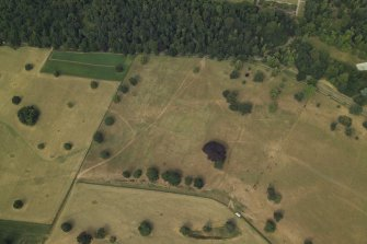 Oblique aerial view centred on the parchmarks of the formal garden, taken from the SE.